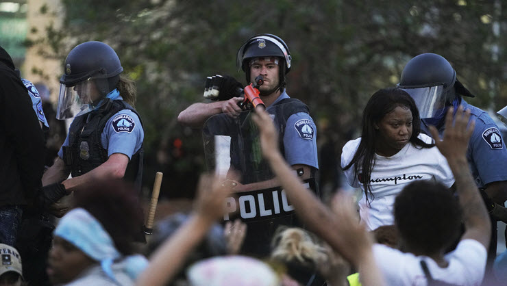 police officer aims weapon at protesters